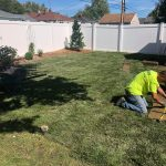 man touching up sod in a backyard